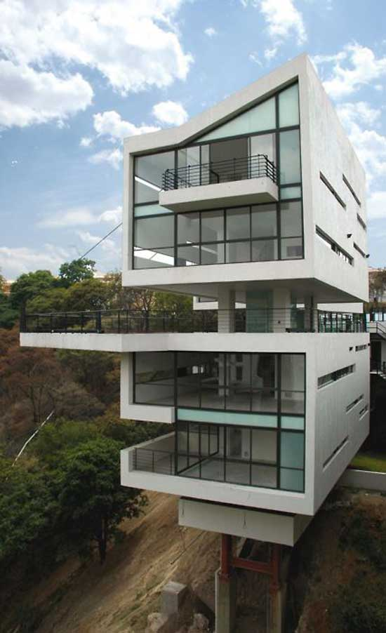 exterior view of a home on several floors with large windows