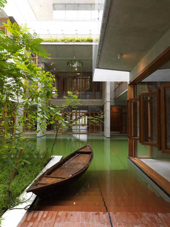 exterior view of a home with a green pool and small boat