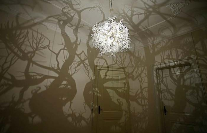 Light sculpture projecting tree shadows on the walls of a room