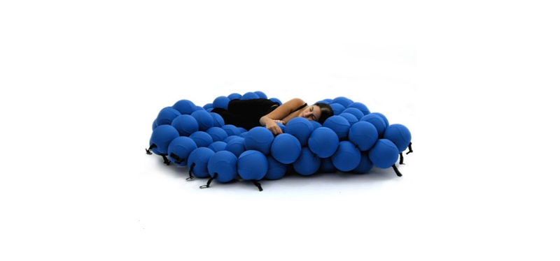 A woman sleeping on a blue Feel Seating Deluxe by Animi Causa