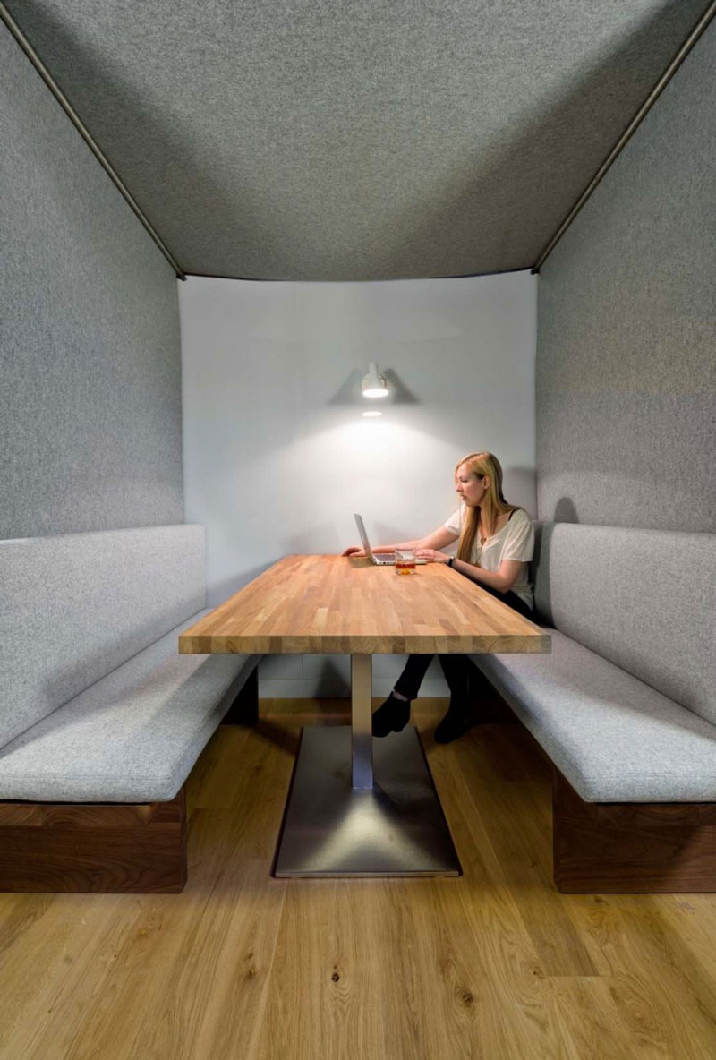Woman in a booth sitting on a cushioned bench at Giant Pixel headquarter in San Francisco