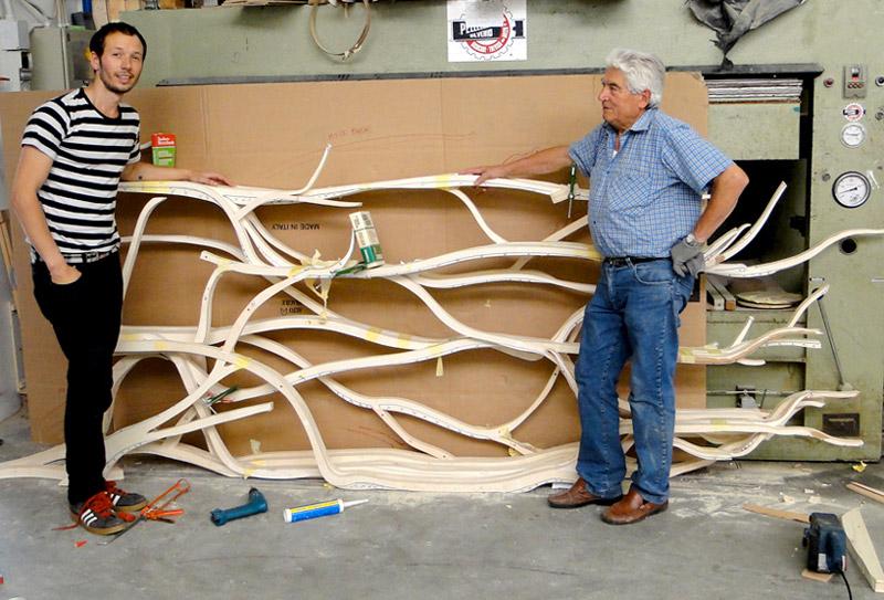 Designer Sebastian Errazuriz and another man with the unfinished Metamorphosis Bookshelf