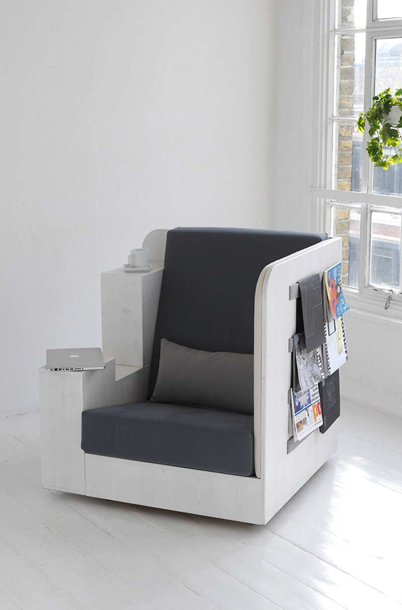 Openbook Armchair by Studio Tilt in a white room with magazines stored on the side of the armchair