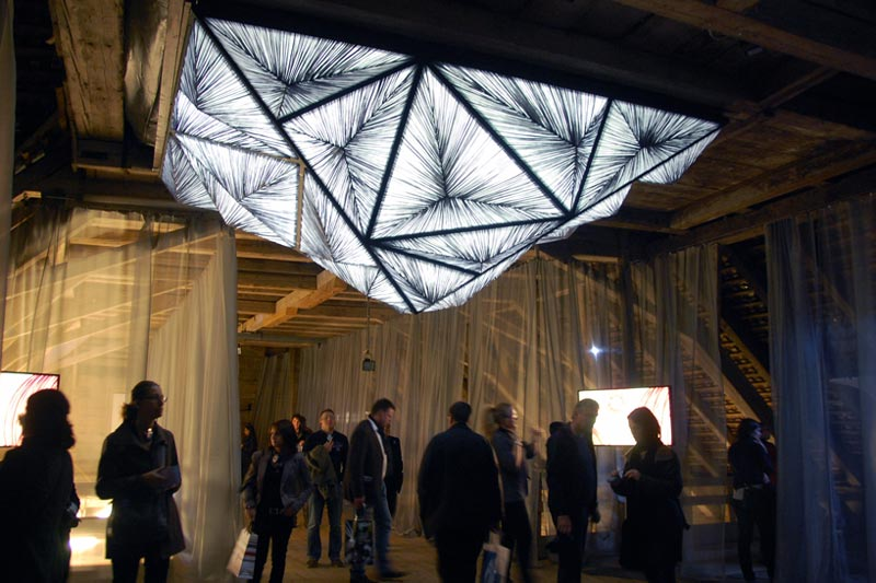 Illuminated white and gray color Pyramid lighting sculpture suspended from the ceiling at an exhibition