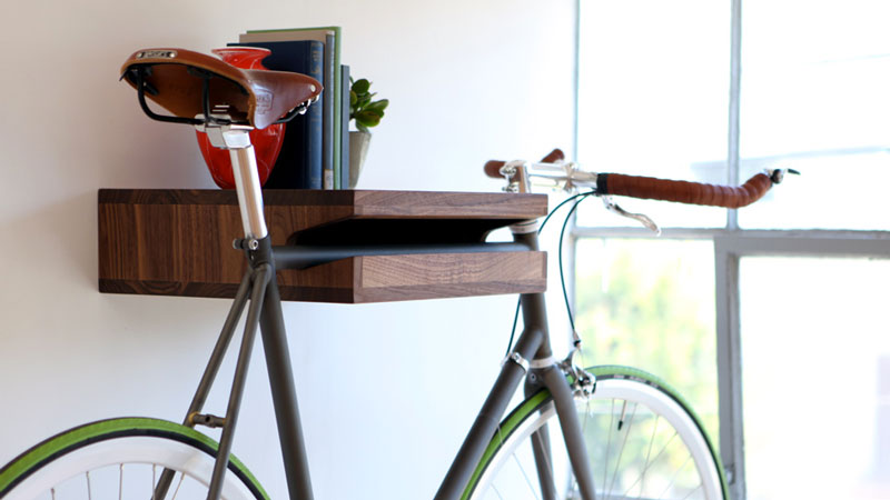 green bicycle suspended on a bookshelf