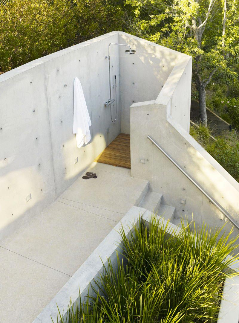 Outdoor shower surrounded by concrete walls at The Banyan Treehouse by Rockefeller Partners Architects