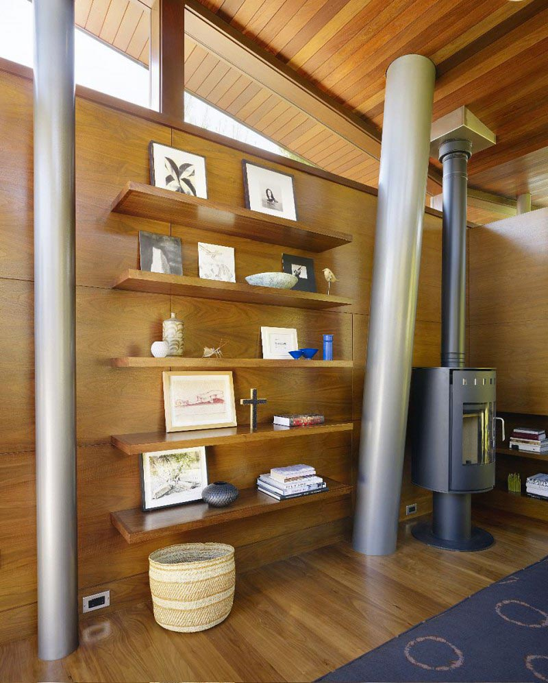 Wooden shelving unit and steel beams and fireplace at The Banyan Treehouse by Rockefeller Partners Architects