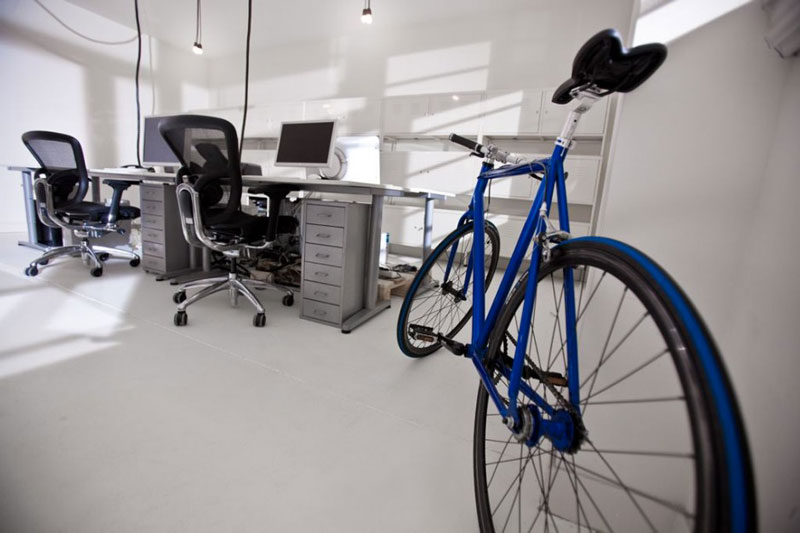 Bicycle, tables and chairs in a room with white walls at the Brandbase Pallet Office by MOST Architecture