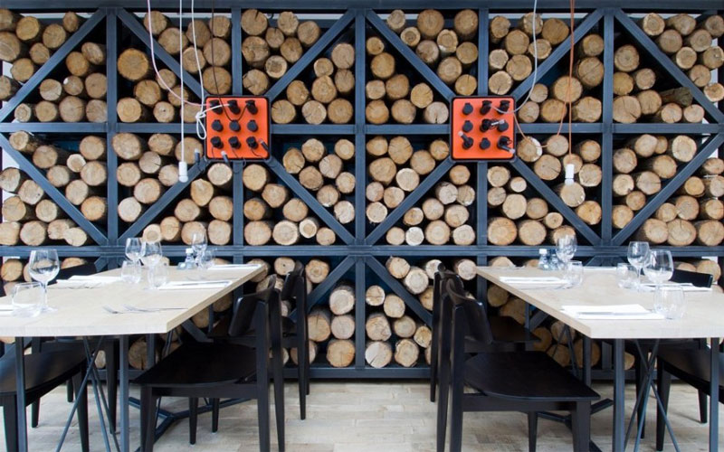 Wall covered with fire logs at the Fabbrica Restaurant in Bergen by Tjep Studio