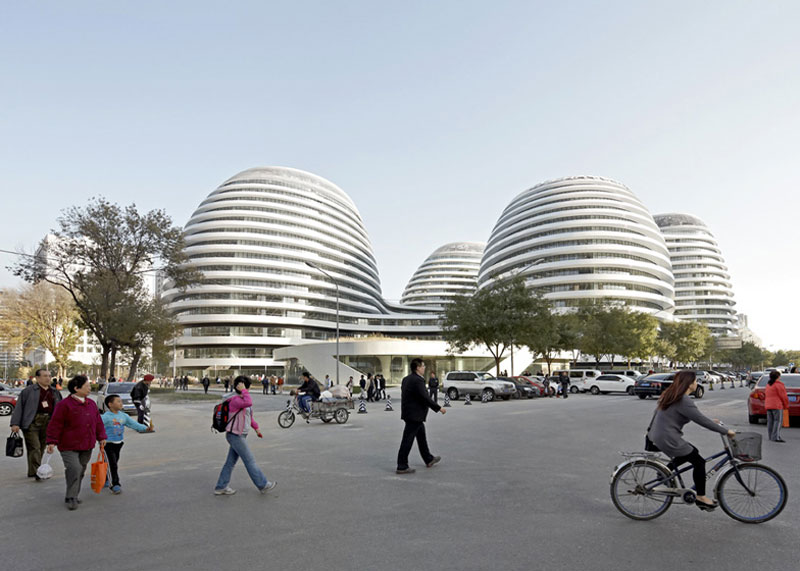 Exterior view during the day of the Galaxy SOHO Complex in Beijing designed by Zaha Hadid with civilians on the ground