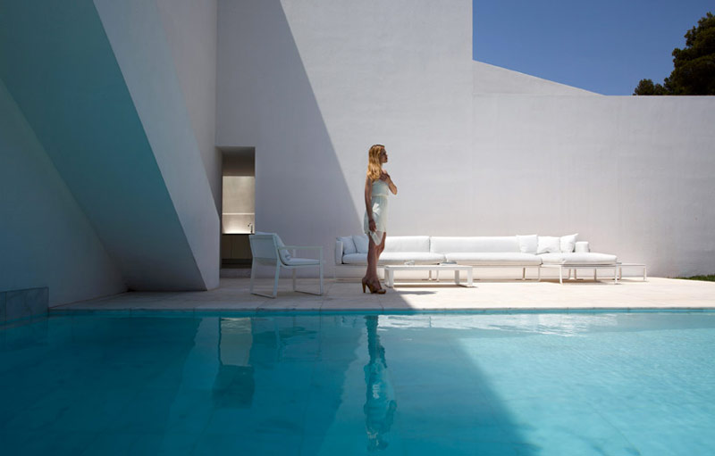 A woman standing next to a white wall and swimming pool