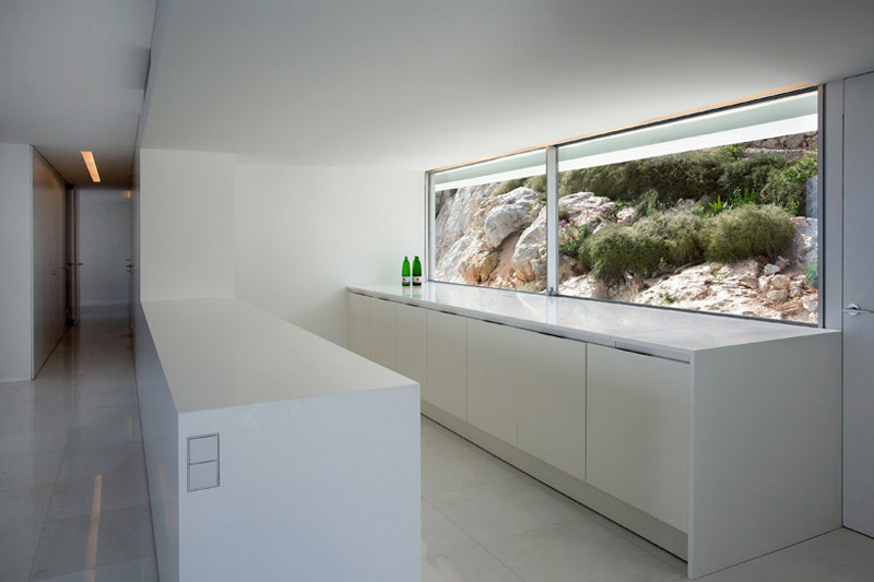 Interior design of the kitchen and window at the House on the Cliff by Fran Silvestre Arquitectos