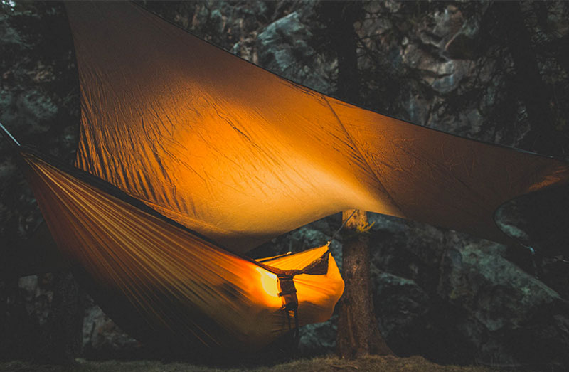 Kammok Glider Rain Tarp and Hammock Weather Relief Shelter set up at night in the forest