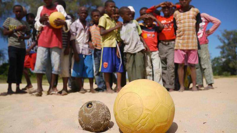 Yellow One World Futbol Soccer ball next to an old soccer ball