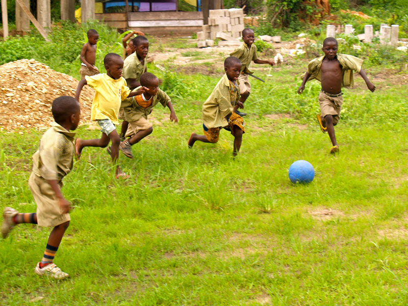 African kids playing with a blue One World Futbol Soccer ball