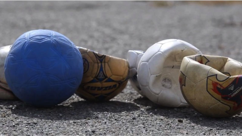 Blue One World Futbol next to damaged and punctured soccer balls