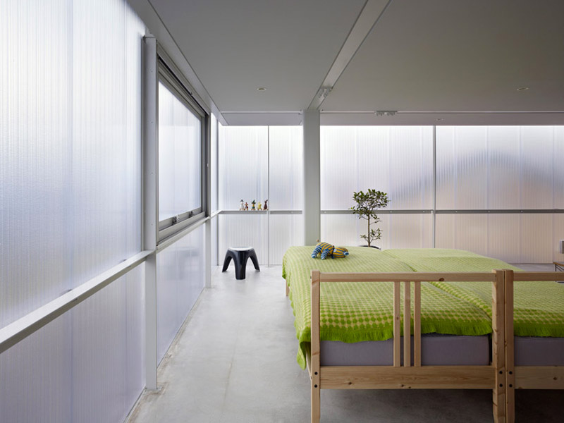 Bed with green covers and semi-transparent windows at the House in Tosuien by Suppose Design Office
