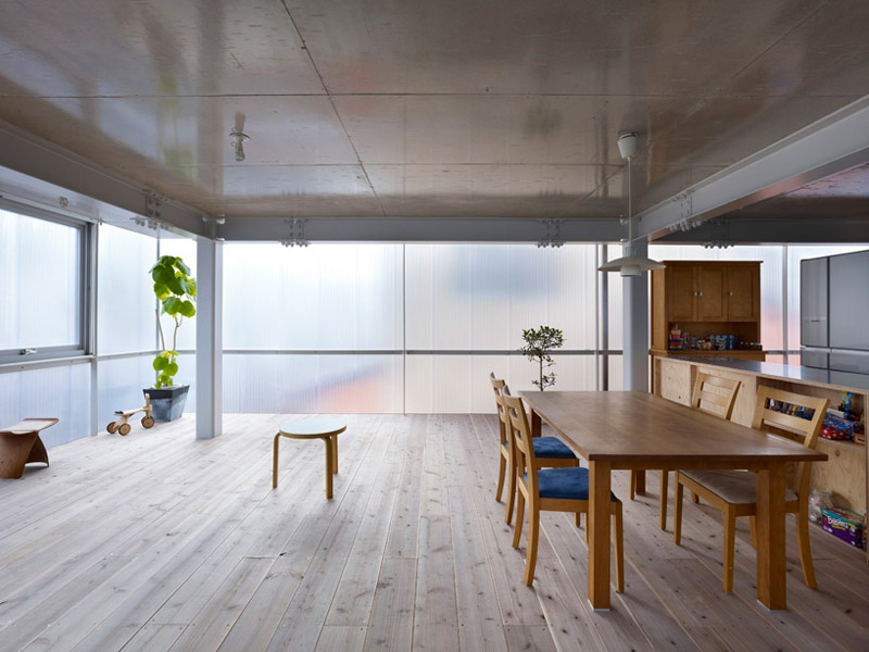 Interior view of the wooden kitchen table and wooden floors at the House in Tosuien by Suppose Design Office