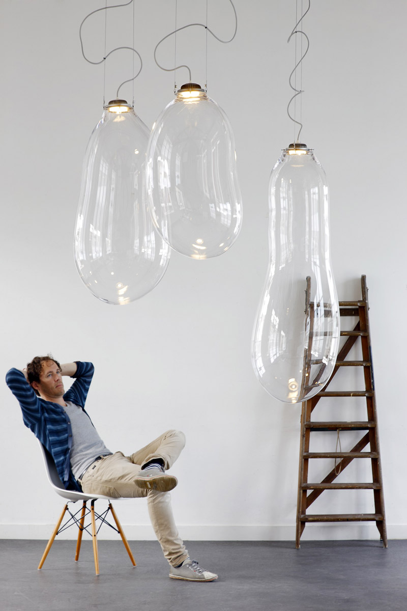 The Big Bubble Light Alex de Witte in a room with white walls and a men sitting on a white wooden chair