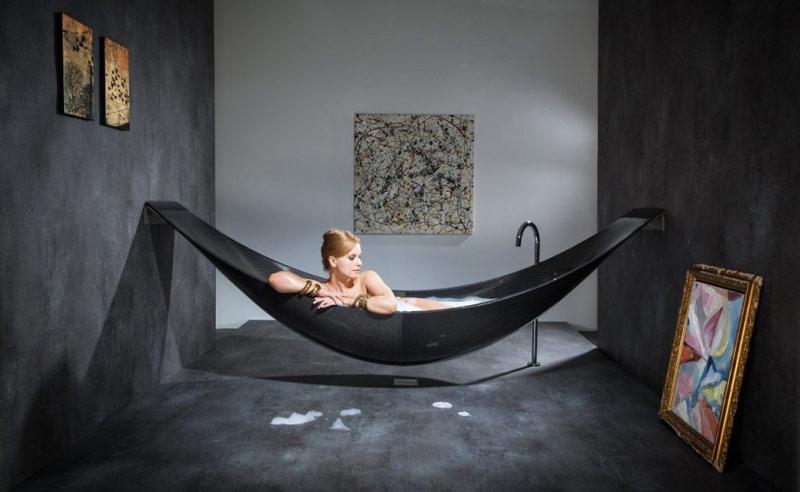 A woman lying down in the Vessel Hammock Bathtub by Splinter Works