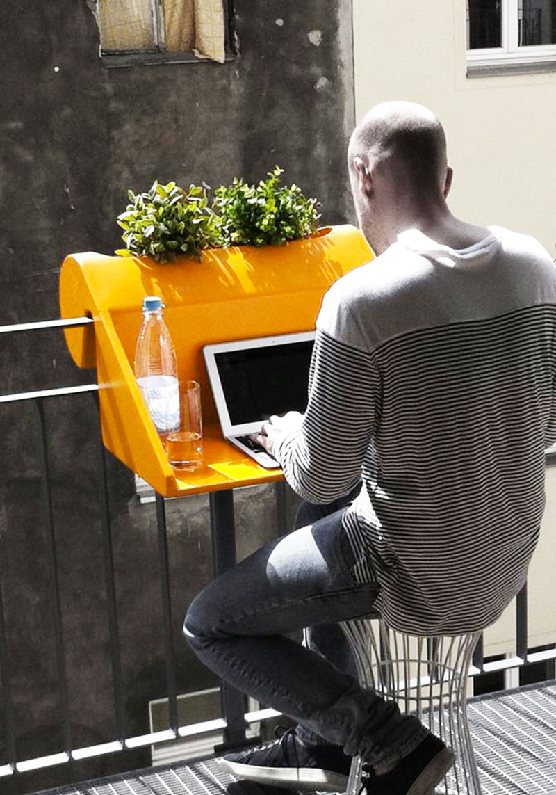 Man sitting and using a computer on the balKonzept Balcony Desk