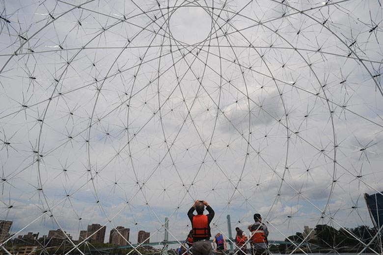 Floating Dome made of discarded umbrellas and plastic bottles by SLO Architecture placed in the Bronx River in New York