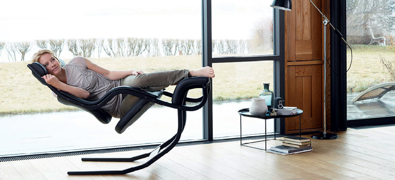 Woman lounging on the Gravity Balans Chair by Varier Furniture