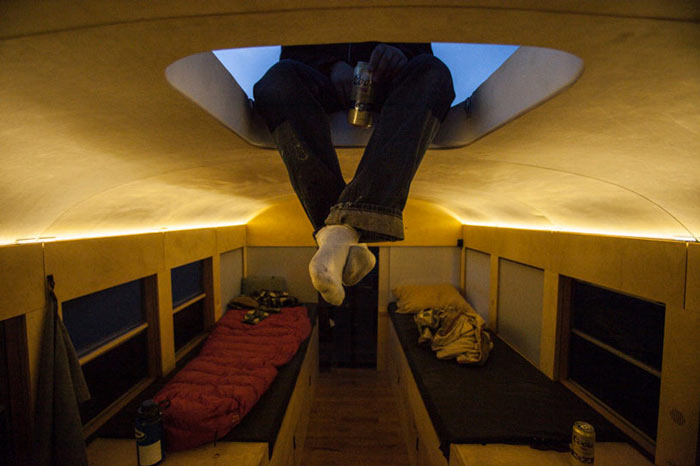 Man sitting on the sunroof of a converted school bus