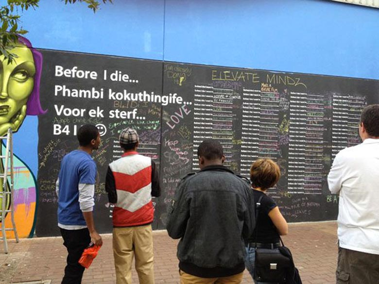 2 women writing on the Before I Die wall by Candy Chang in Johannesburg South Africa