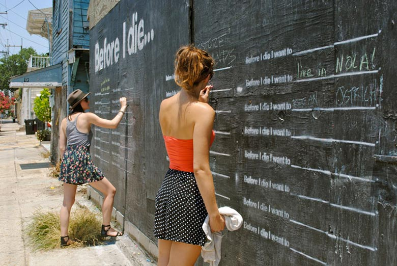 2 women writing on the Before I Die wall by Candy Chang
