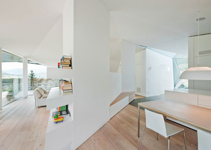 White walls and wooden floors of the interior of the Paramount Alma Residence by Plasma Studio