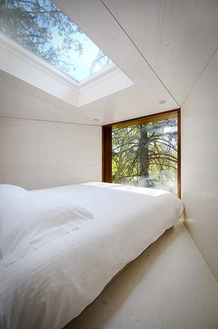 Bedroom with a white bed and skylight at the Tree Snake Houses in Pedra Salgadas Portugal