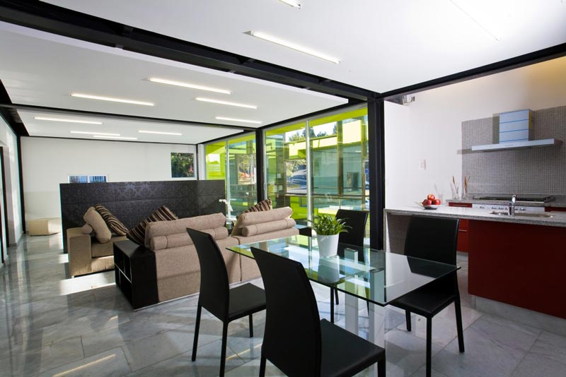 Glass table and black chairs at the Trevox 223 Reflective Building by CRAFT Arquitectos