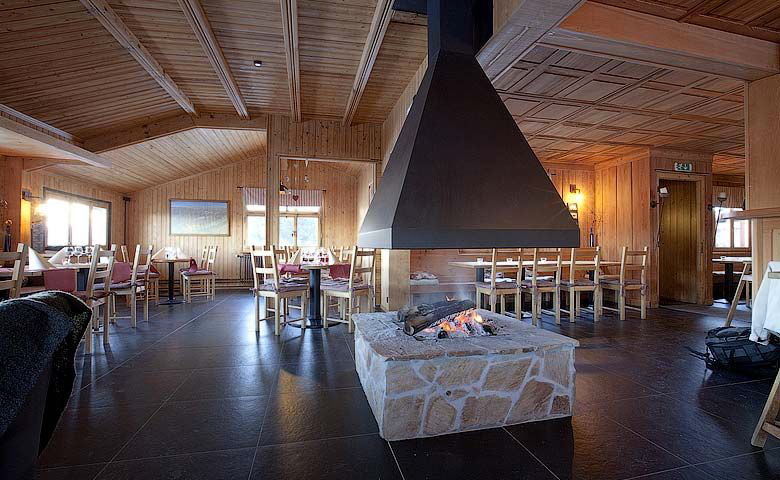Interior design of the Whitepod Hotel in the Swiss Alps in Switzerland with a fireplace at the center of the room