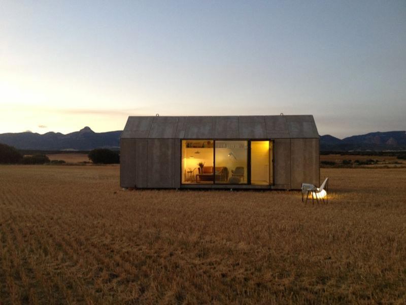 aph80 Portable Concrete Prefab House by Abaton placed in a field