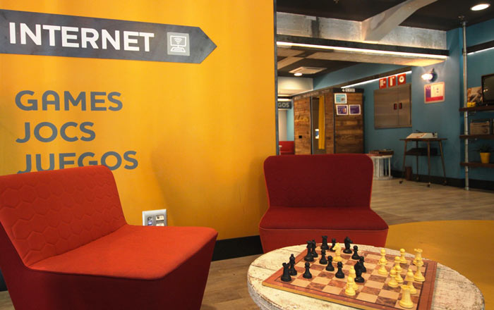 Interior design with a red chair and a chess board on a circular table at Generator Hostel in Barcelona Spain