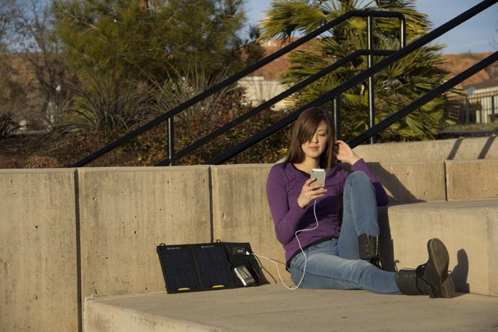 Woman charging her phone using the Guide 10 Plus Solar Charging Kit by Goal Zero