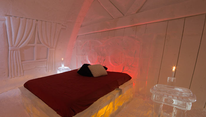 Bedroom with a bed and red sheets at the Hotel de Glace, An Ice Hotel Quebec City, Canada