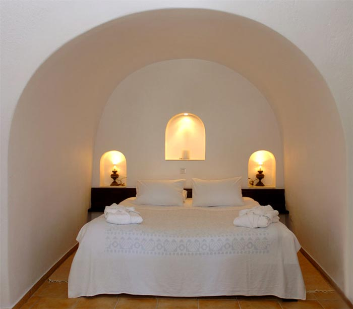 Bed in bedroom at the Ikies Traditional Houses in Santorini