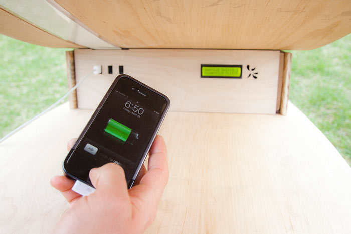 iPhone being charged by the MIT SOFT Rockers Solar Powered Charging Station & Rocking Chair