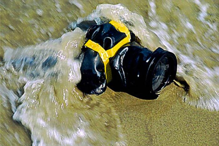OUTEX SLR Camera Drysuit Kit on a sandy beach surrounded by water