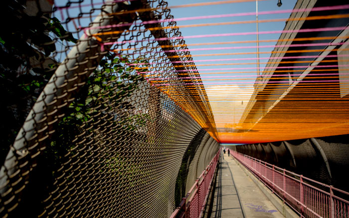 Yarn tied to a fence at the Williamsburg Bridge, a project from HOT TEA