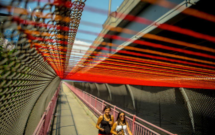 Yarn tied to the fence and Williamsburg Bridge, a project by HOT TEA
