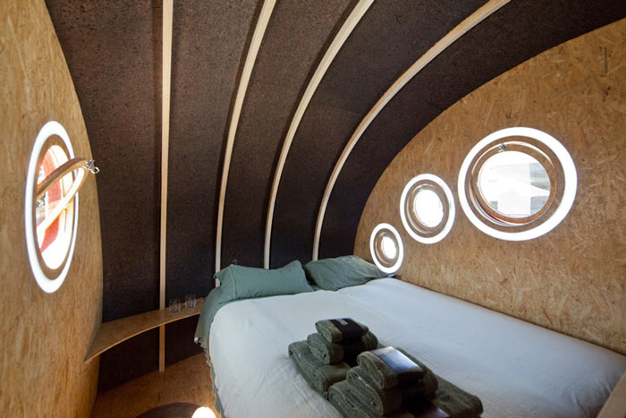 Bed with whie sheets and green pillows at Shelter ByGG Portable Accommodation by Gabriela Gomes
