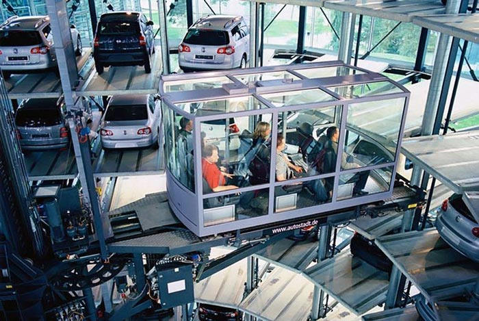 People being transported within the Architecture at night of the Volkswagen Car Park at AutoStadt by HENN Architekten