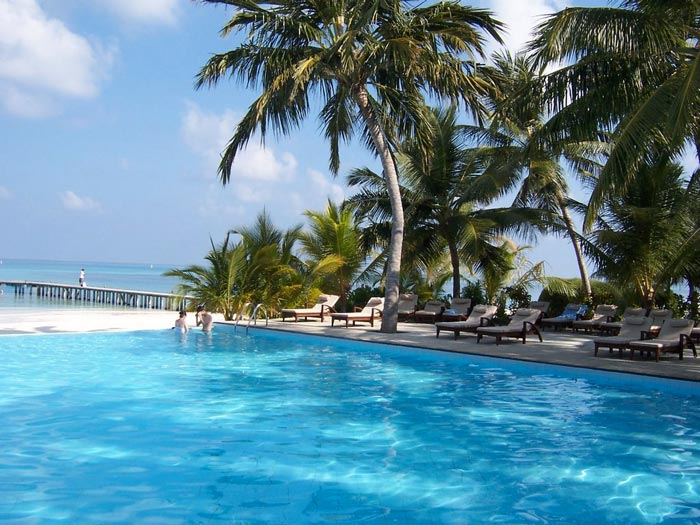 Swimming pool and palm trees at Club Med Kani Family Resort in The Maldives