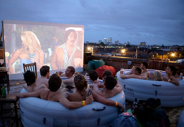 People watching a movie in Hot Tubs at the Rooftop Cinema at Rockwell House in London