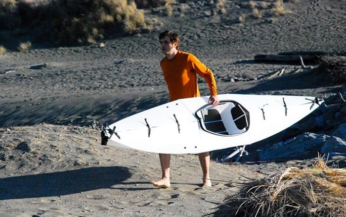 Man carrying the Oru Kayak - A Portable Origami Folding Boat on a beach