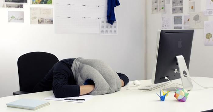 Man using the Ostrich Pillow by Studio Banana Things and kawamura-ganjavian at the office