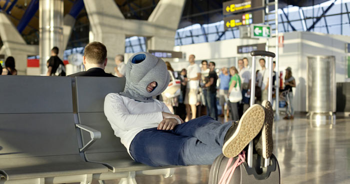 Man using the Ostrich Pillow at the airport
